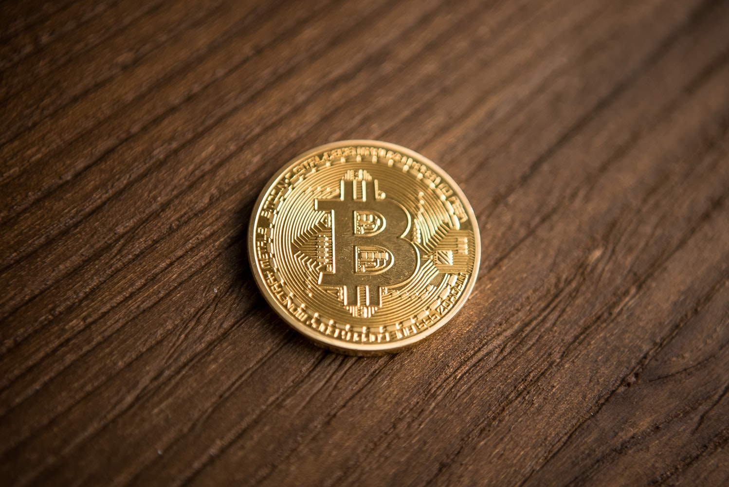 A coin with the symbol of Bitcoin. Bitcoin is a digital currency, so a physical form of it has no meaning.